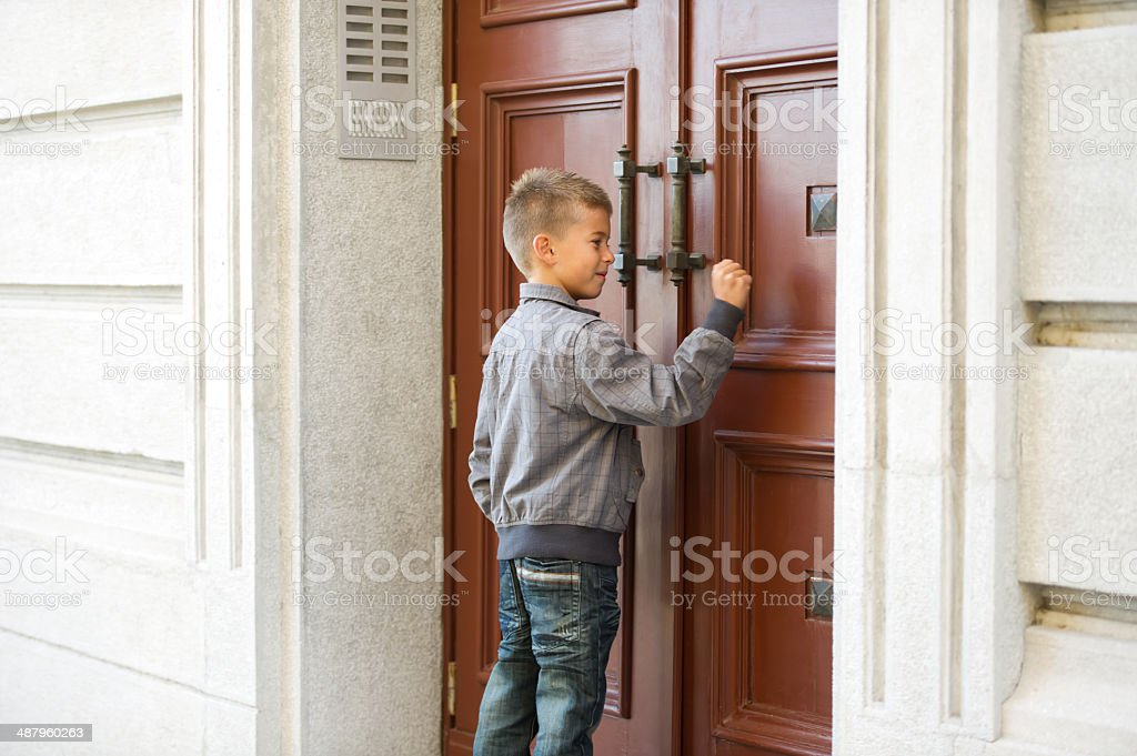Little Boy Knocking The Door stock photo