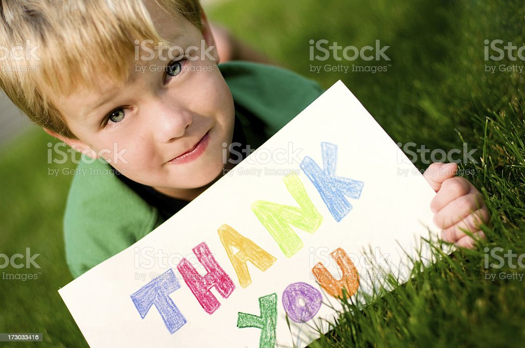 Little boy laying in grass holding a colored thank you sign royalty-free stock photo