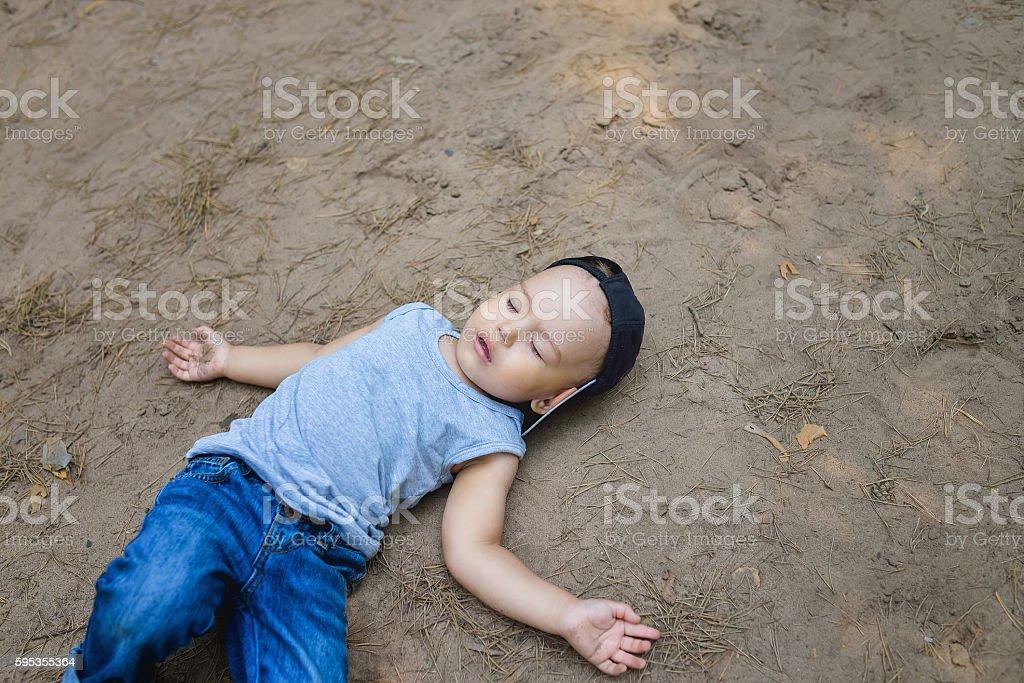 Little boy laying on ground pretending sleep or unconscious - foto de stock
