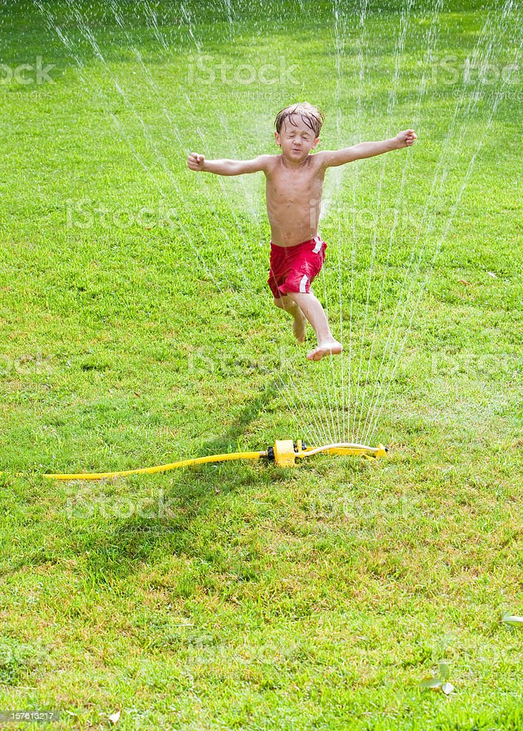 Little Boy Leaping in a Sprinkler royalty-free stock photo