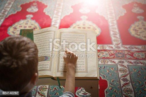 istock little boy learn Quran 624140262