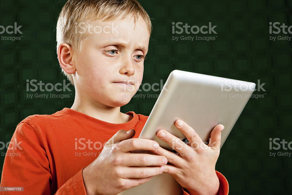 Little boy learning how to use tablet-style pc royalty-free stock photo