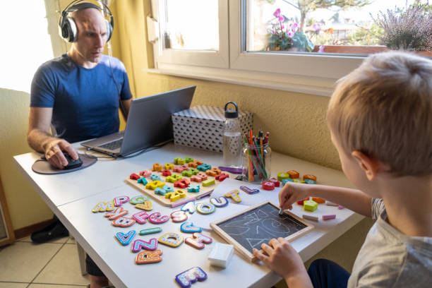 Little Boy learning numbers and letters while his Dad works from home Little Boy learning numbers while his Dad works from home image stock pictures, royalty-free photos & images