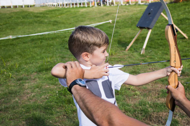 Little boy learning to aim with bow and arrow.