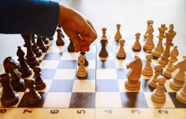 kleiner junge schach spielen lernen - kindergarten workshop stock-fotos und bilder
