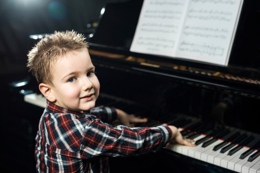 Little boy learning to play the piano.