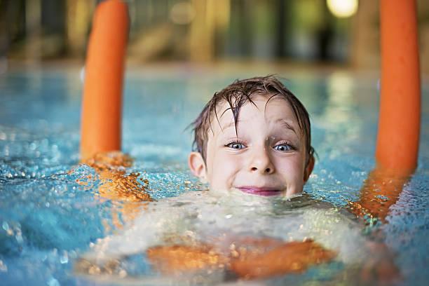 Niño aprendiendo a nadar en la piscina con fideos - foto de stock