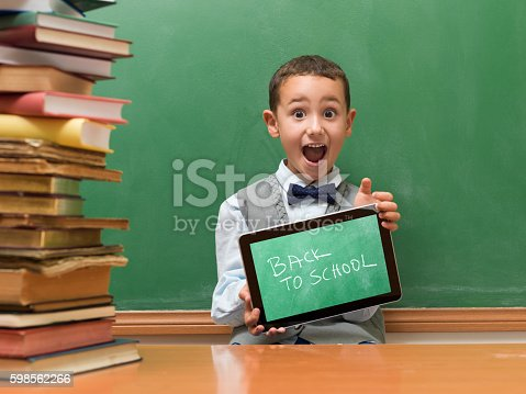 istock Little boy leaving books and using digital tablet 598562266