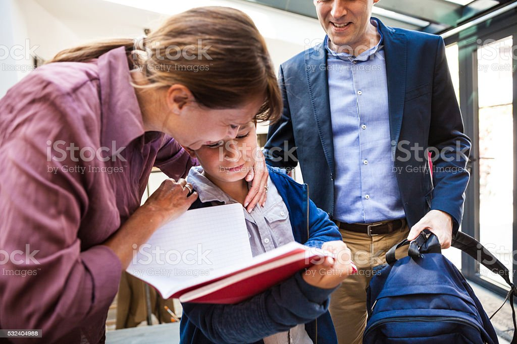 Little boy leaving for school with parents in the morning stock photo