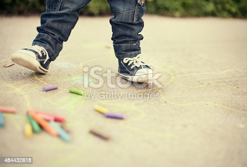 istock Little boy legs and sidewalk chalks 484432618
