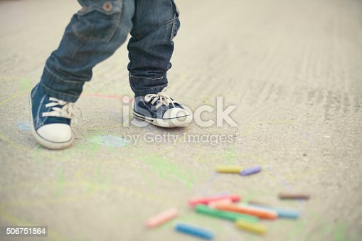 istock Little boy legs and sidewalk chalks 506751864
