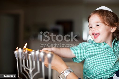 Little boy helping light the Hanukkah menorah