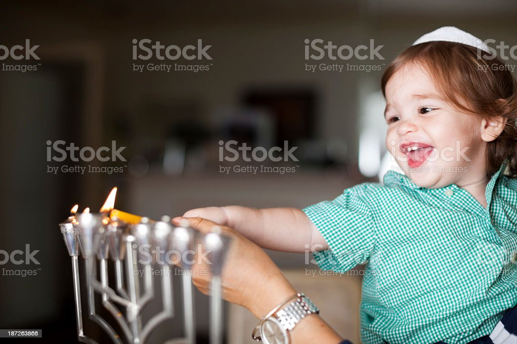 Little boy lighting a silver Menorah stock photo