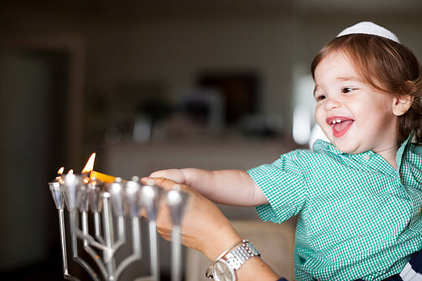 Little boy lighting a silver Menorah Little boy helping light the Hanukkah menorah judaism stock pictures, royalty-free photos & images
