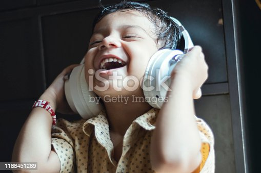 Indian Smiling little boy using phone.indoor shoot at home. The 3 year old boy is wearing white headphones.