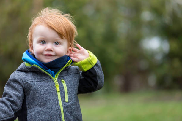 Little Boy Listening to Nature Sounds Outdoors stock photo
