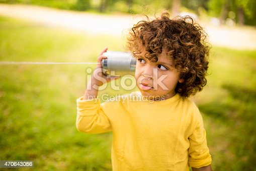 Interested little boy listening to sound vibrations coming through a tin can phone in a park