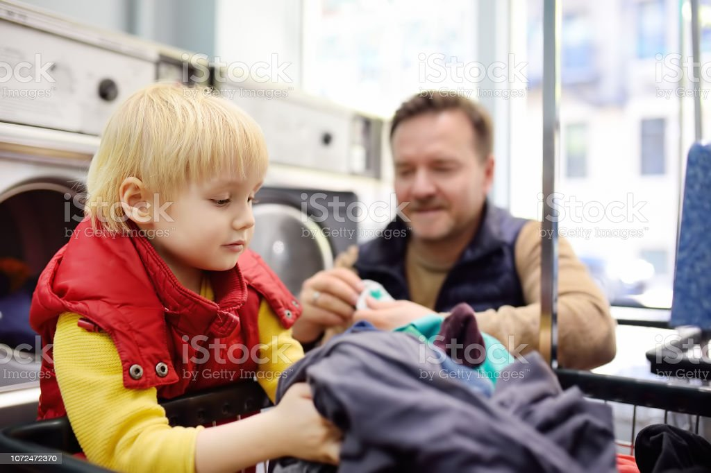 A little boy loads clothes into the washing machine in public laundrette stock photo