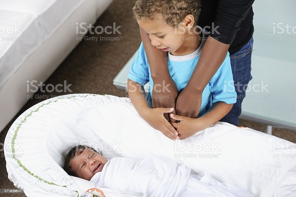 Little Boy Looking At  Baby Sister Under Carer's/ Mother's Supervision royalty-free stock photo
