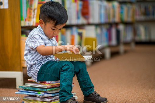 A little boy is sitting on a stack of books at the library and is reading.