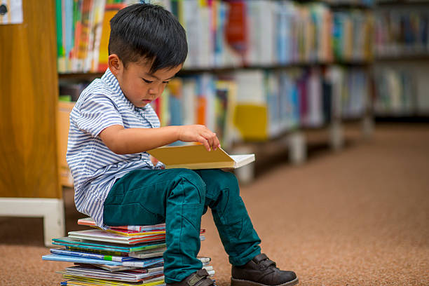 Little Boy Looking at Books - foto de acervo