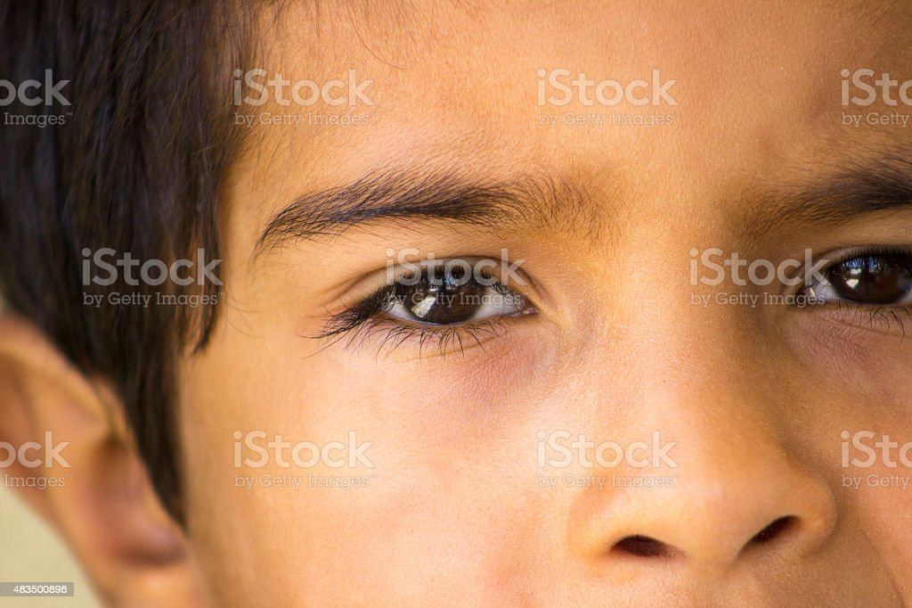 Little boy looking at camera in thought stock photo