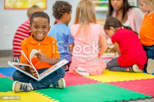 A little boy in preschool is sitting on a foam mat with her classmates and is holding a picture book - he is smiling and looking at the camera.