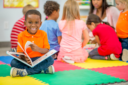 Little Boy Looking at Picture Book in Preschool stock photo