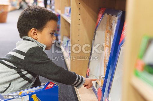 A candid photograph of a 3-year old eurasian boy looking at a toy crane on the shelf of a toy store