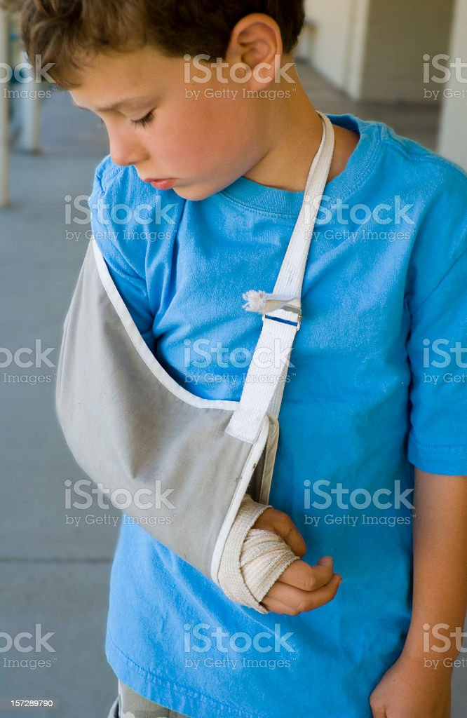 Little boy looking down at his broken arm royalty-free stock photo