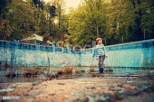 Little boy wearing galoshes is playing in a dirty old abadoned swimming pool. The boy is looking for frogs in a small pond on the base of swimming pool.