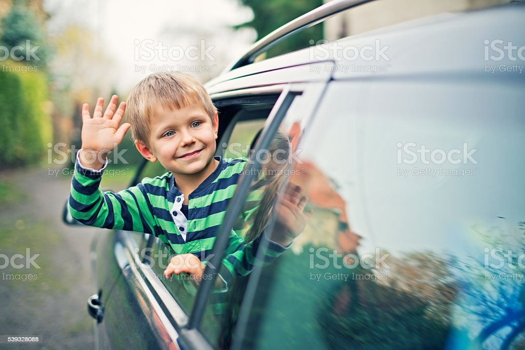 Little boy looking out of the car window and waving stock photo