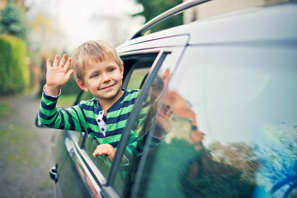 little boy looking out of the car window and waving - separation stock photos and pictures