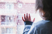 Little boy looking out of the window on a snowy day
