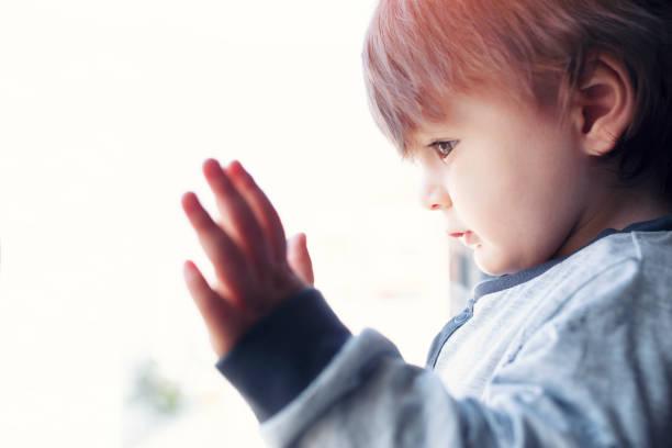 kleiner junge aus dem fenster - autismus stock-fotos und bilder