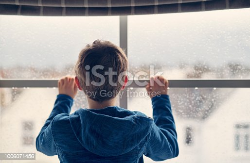 Little boy looking out of window on rainy day.  Nikon D850