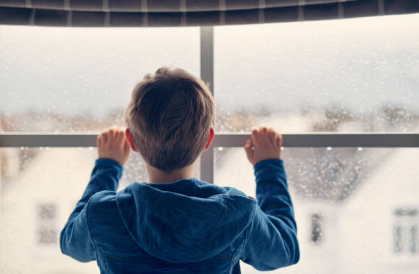 little boy looking out of window on rainy day - boy looking out window stock pictures, royalty-free photos & images