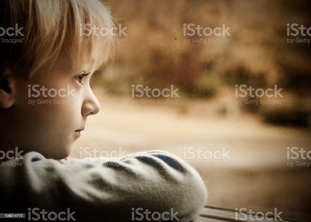 Little Boy Looking Out the Window at Rain royalty-free stock photo