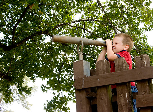 Little boy looking through a tube by a wooden gate stock photo