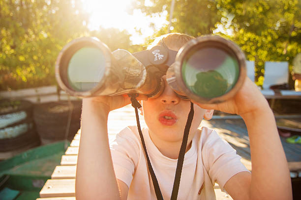 little boy looking through binoculars on river bank - boy looking out window stock pictures, royalty-free photos & images