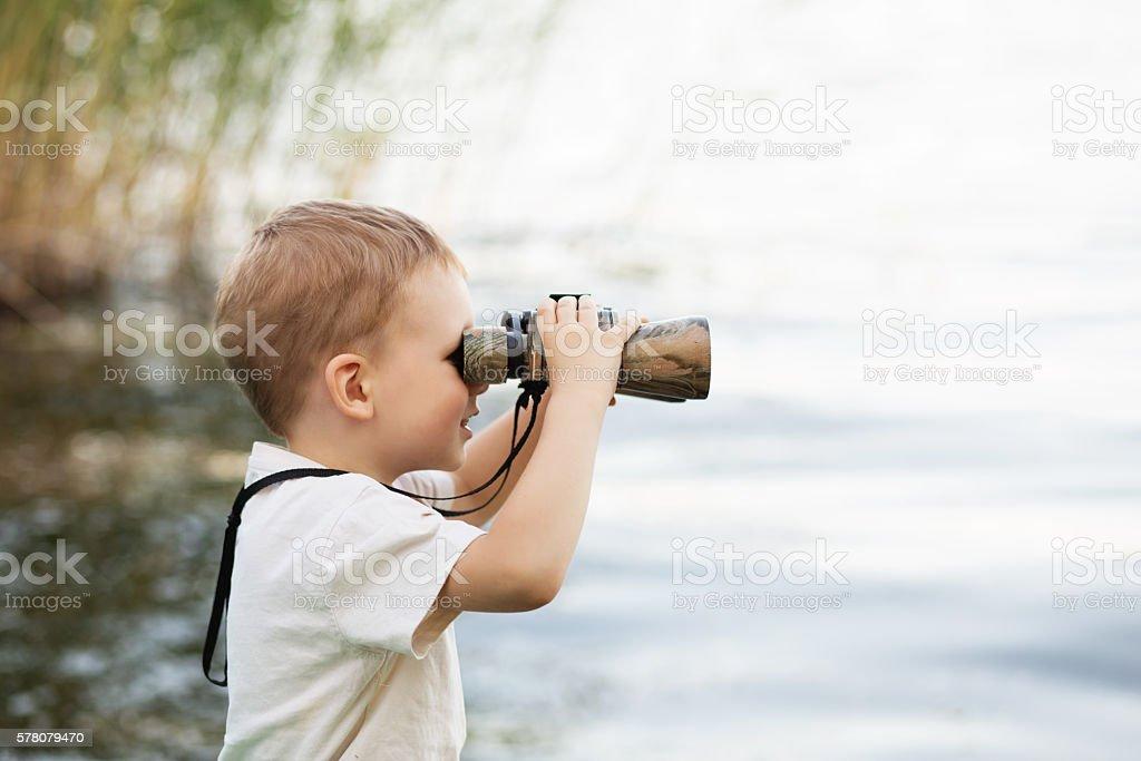 Little boy looking through binoculars on river bank stock photo
