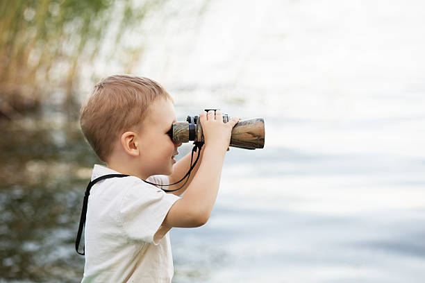little boy looking through binoculars on river bank - binocular boy bildbanksfoton och bilder
