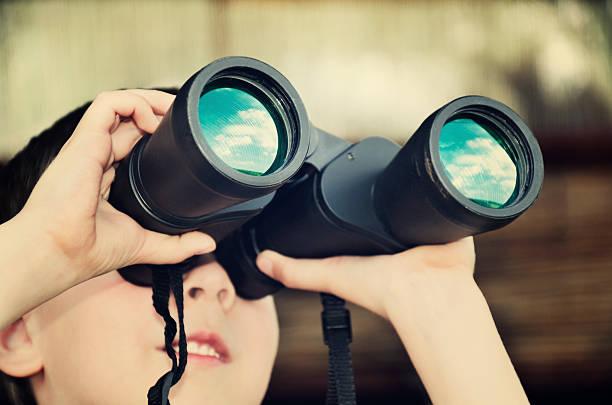 Kleiner Junge schaut durch binoculars. getönte Vanille Effekt Bild mit – Foto