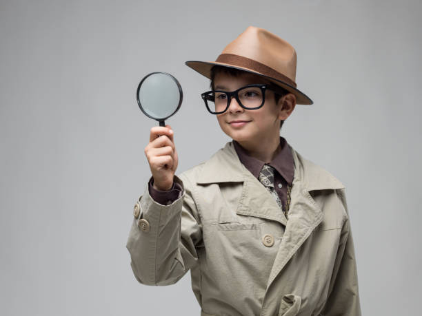 little boy looking through magnifying glass - sherlock holmes stock photos and pictures