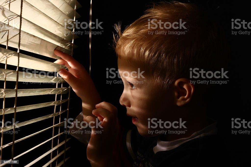 Little boy looking through window blinds stock photo