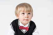 Little boy looking up on gray background