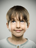 Close up portrait of cute little boy looking up on gray background. Vertical shot of real kid in studio. Photography from a DSLR camera. Sharp focus on eyes.