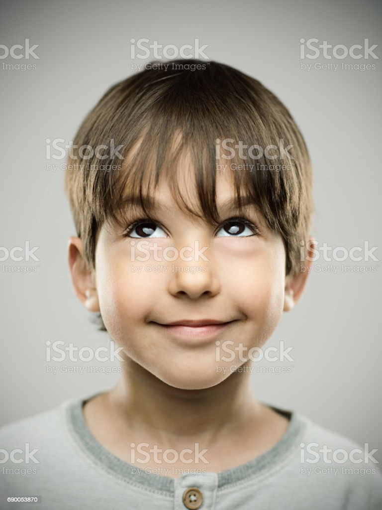 Little boy looking up on gray background stock photo