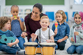 istock Little boy looks into camera as he plays the bongos 1168447350