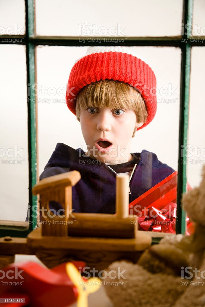 Little boy looks toy shop window. Antique toys display. Christmas. stock photo
